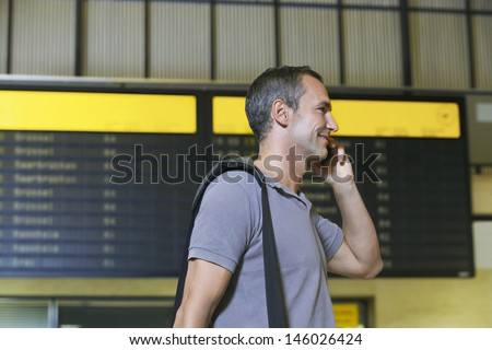 Side view of a male traveler using mobile phone in front of flight status board in airport - stock photo