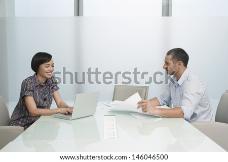 Side view of a man and smiling woman working in conference room with documents and laptop - stock photo
