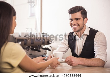 Side view of a man barista giving cup of coffe to woman at counter in the coffee shop. - stock photo