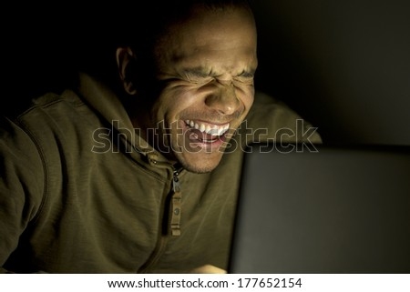 Side view of a man laughing whilst using his laptop at night, concept of modern technology use - stock photo