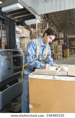 Side view of a man making notes in distribution warehouse - stock photo