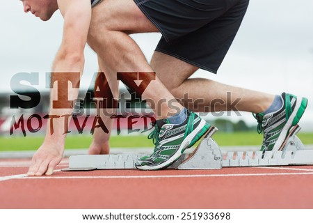 Side view of a man ready to race on running trac against stay motivated - stock photo