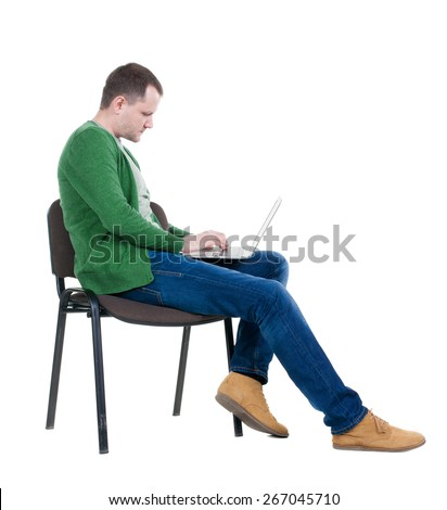 Side view of a man sitting on a chair to study with a laptop. Isolated  over white background - stock photo