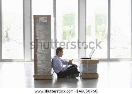 Side view of a man with mobile phone and laptop between packages in empty office - stock photo