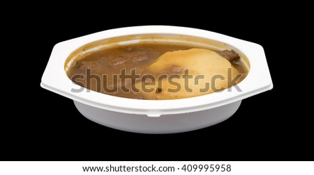 Side view of a mashed potatoes in gravy with beef tips TV dinner in the plastic tray on a black background. - stock photo