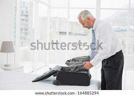 Side view of a mature businessman unpacking luggage at a hotel bedroom