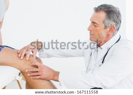 Side view of a mature doctor examining patients knee at the medical office - stock photo