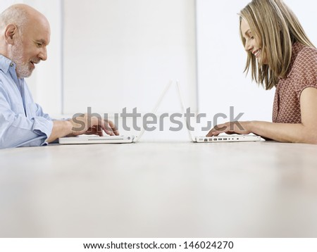 Side view of a mature man and woman using laptops on table - stock photo