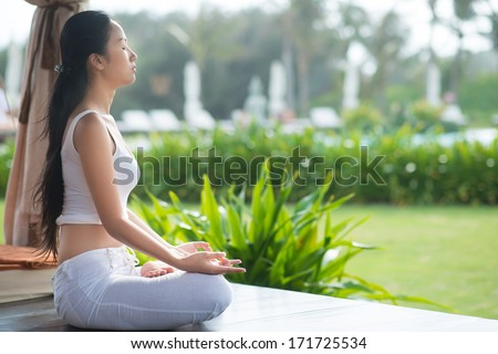 Side view of a meditating woman - stock photo