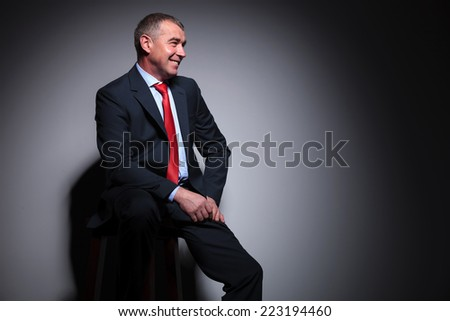 Side view of a mid aged business man sitting on a stool, lookin away from the camera.