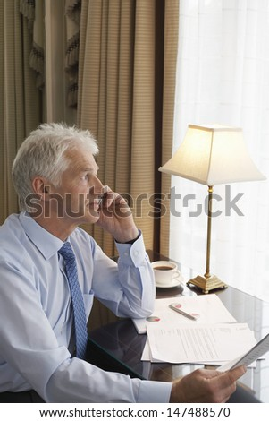 Side view of a middle aged businessman on call at home desk - stock photo