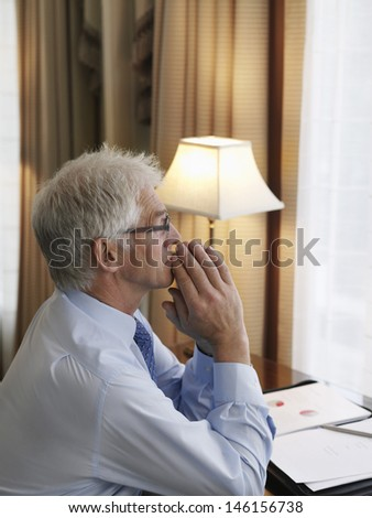 Side view of a middle aged businessman with hands folded sitting at desk - stock photo