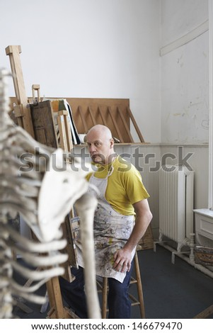 Side view of a middle aged male artist painting in studio - stock photo