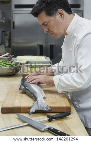 Side view of a middle aged male chef preparing salmon in kitchen - stock photo