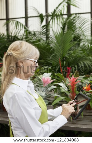 Side view of a middle-aged using tablet pc in greenhouse