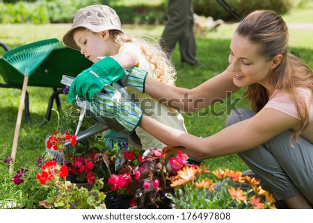 Side view of a mother and daughter watering plants at the garden - stock photo