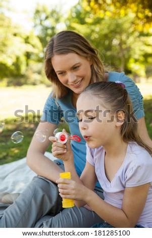 Side view of a mother with her daughter blowing soap bubbles at the park - stock photo