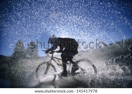 Side view of a mountain bicyclist splashing through water - stock photo