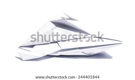 Side view of a nice origami spaceship isolated over a sheet of paper - stock photo