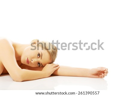 Side view of a nude woman lying on hands on the floor, looking at the camera