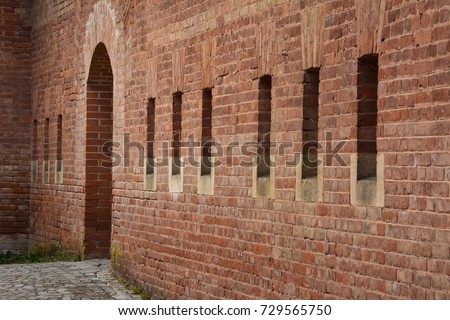 Side View Of A Old Red Brick Building Wall With Small Windows And Big Entry