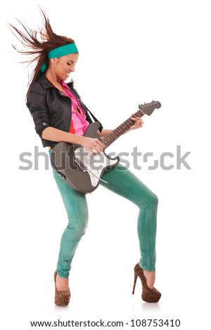side view of a passionate woman guitarist playing rock and roll on an electric guitar - stock photo