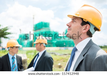 Side view of a pensive engineer on the foreground - stock photo