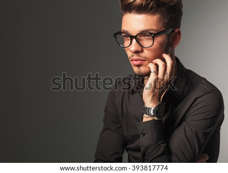side view of a pensive young man with glasses looking away