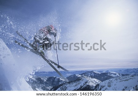Side view of a person on skis jumping over slope - stock photo