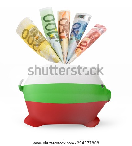 Side view of a piggy bank with the flag design of Bulgaria and various european banknotes.(series) - stock photo