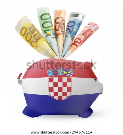 Side view of a piggy bank with the flag design of Croatia and various european banknotes.(series) - stock photo