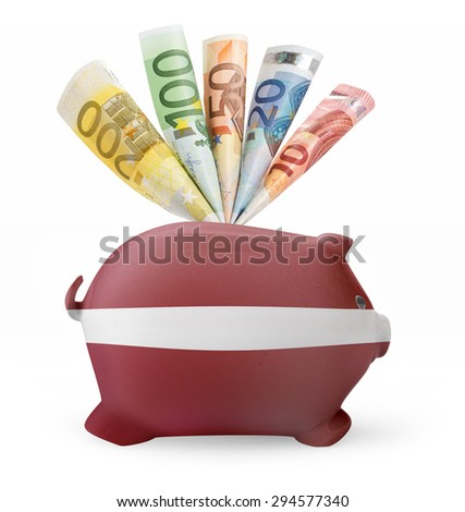 Side view of a piggy bank with the flag design of Latvia and various european banknotes.(series) - stock photo