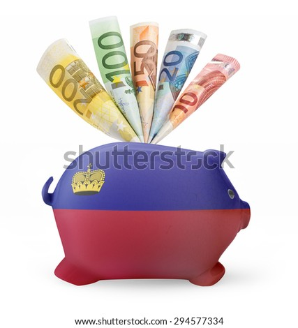 Side view of a piggy bank with the flag design of Lichtenstein and various european banknotes.(series) - stock photo