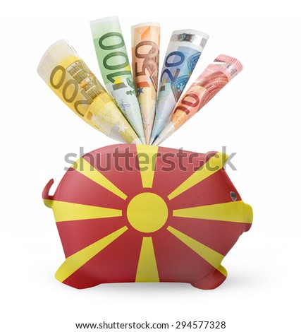 Side view of a piggy bank with the flag design of Macedonia and various european banknotes.(series) - stock photo