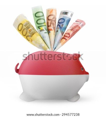 Side view of a piggy bank with the flag design of Monaco and various european banknotes.(series) - stock photo