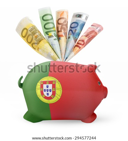 Side view of a piggy bank with the flag design of Portugal and various european banknotes.(series) - stock photo