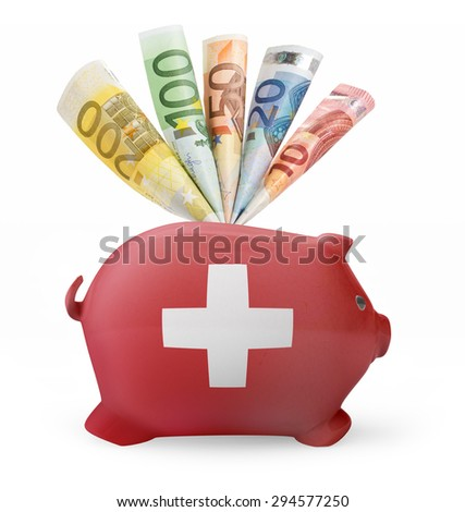 Side view of a piggy bank with the flag design of Switzerland and various european banknotes.(series) - stock photo