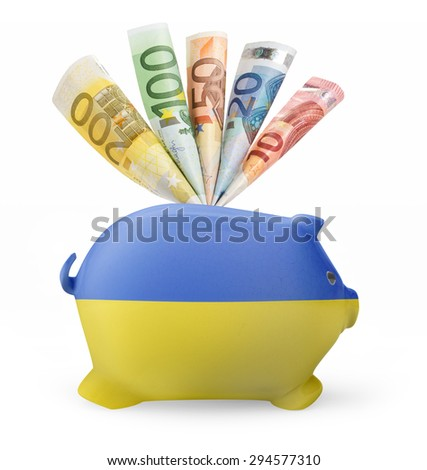 Side view of a piggy bank with the flag design of Ukraine and various european banknotes.(series) - stock photo