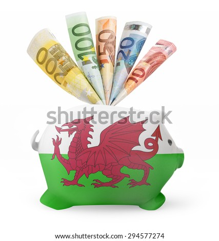 Side view of a piggy bank with the flag design of Wales and various european banknotes.(series) - stock photo