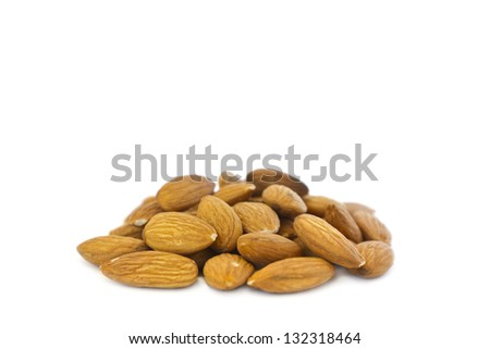 Side view of a pile of organic almonds on white background.