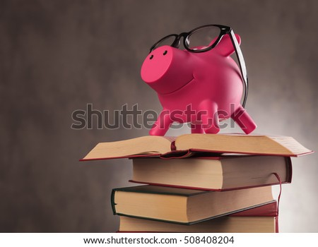 side view of a pink piggy bank wearing glasses and standing on a pile of books - education pays off concept