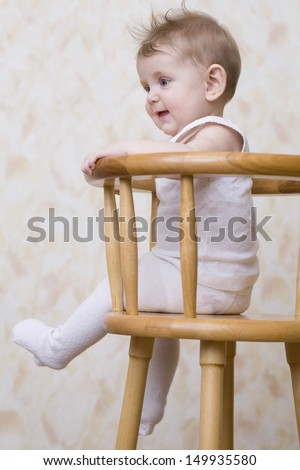 Side view of a playful baby boy sitting on high chair - stock photo
