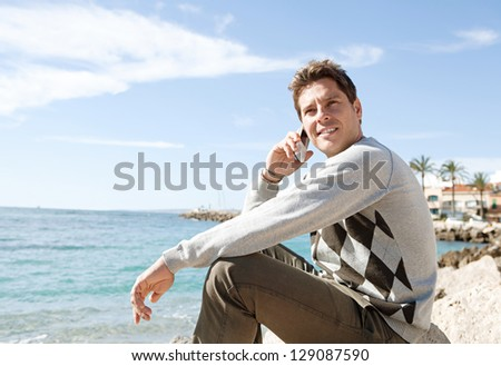 "Side view of a professional man sitting on a rock on the beach having a phone conversation on his ""smart phone"" during a sunny day, smiling. - stock photo"