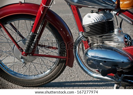 Side view of a red veteran motorbike. - stock photo