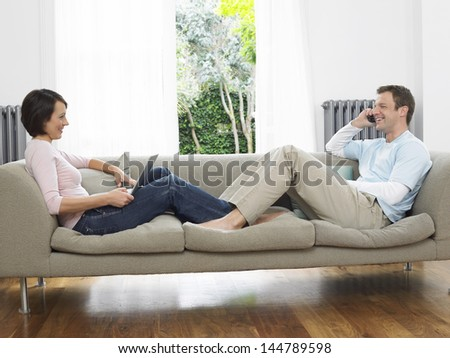 Side view of a relaxed couple using laptop and cellphone on couch - stock photo
