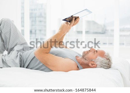Side view of a relaxed mature man using digital tablet in bed at home - stock photo