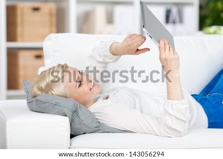 Side view of a relaxed young woman lying on sofa with tablet at home - stock photo