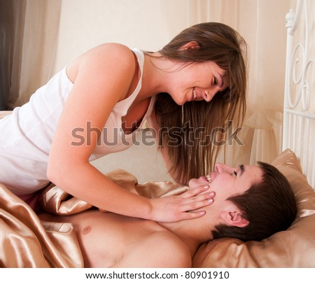 Side view of a romantic couple having fun in bed - stock photo
