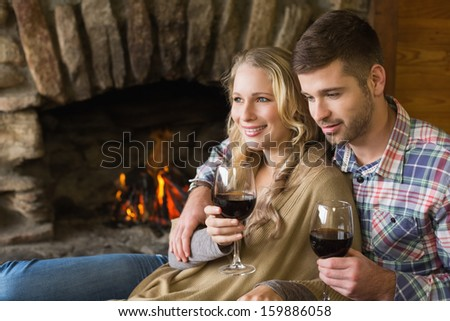 Side view of a romantic young couple with wineglasses in front of lit fireplace - stock photo