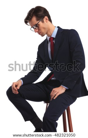 side view of a seated business man with glasses thinking and looks down on white studio background